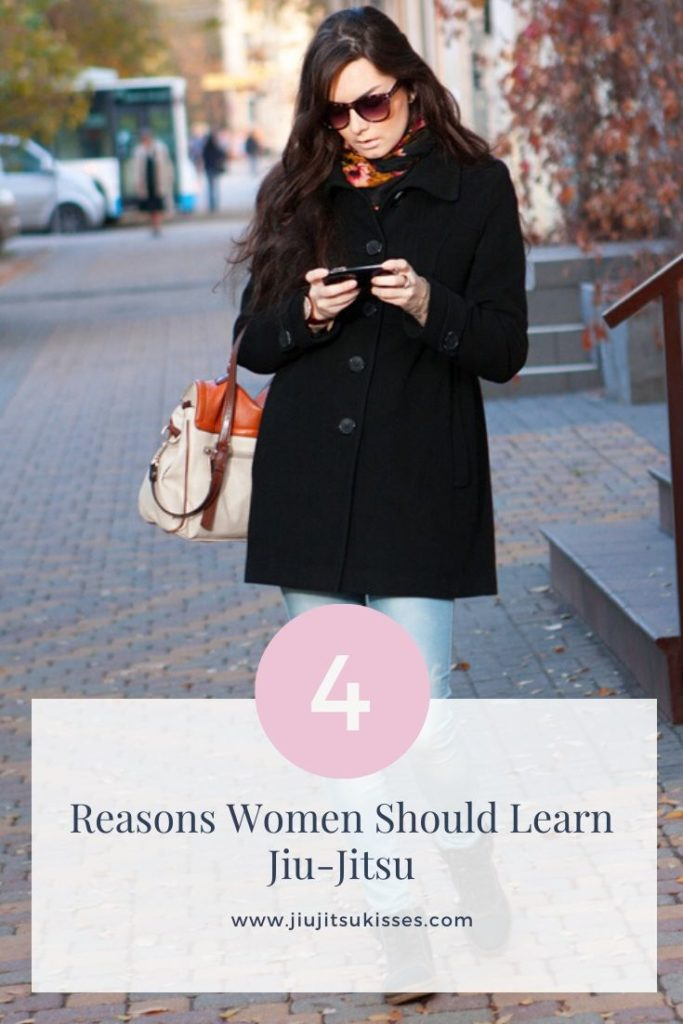 Image of a woman walking down the street looking at her phone
