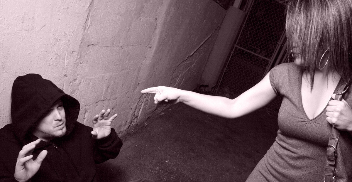 image of a woman pointing her finger at a man on the ground in a black hoodie