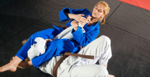image of a woman in a blue gi submitting a person in a white gi with an arm bar