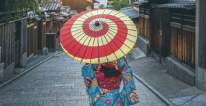image of a Japanese woman in traditional blue kimono with flowers and an orange and yellow umbrella