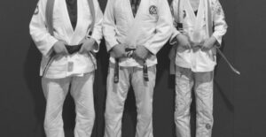 three martial artists holding their belts in grey scale