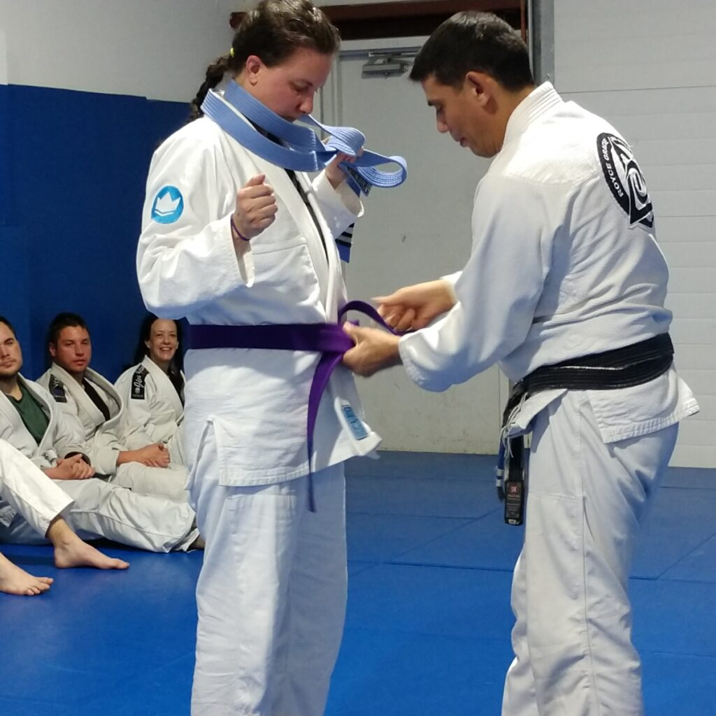 a woman in a white gi holding a blue belt while a male black belt instructor presents her with a new purple belt